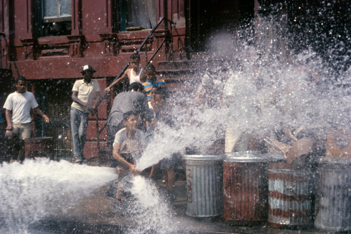 Kids play in water from hydrant in street 1980s