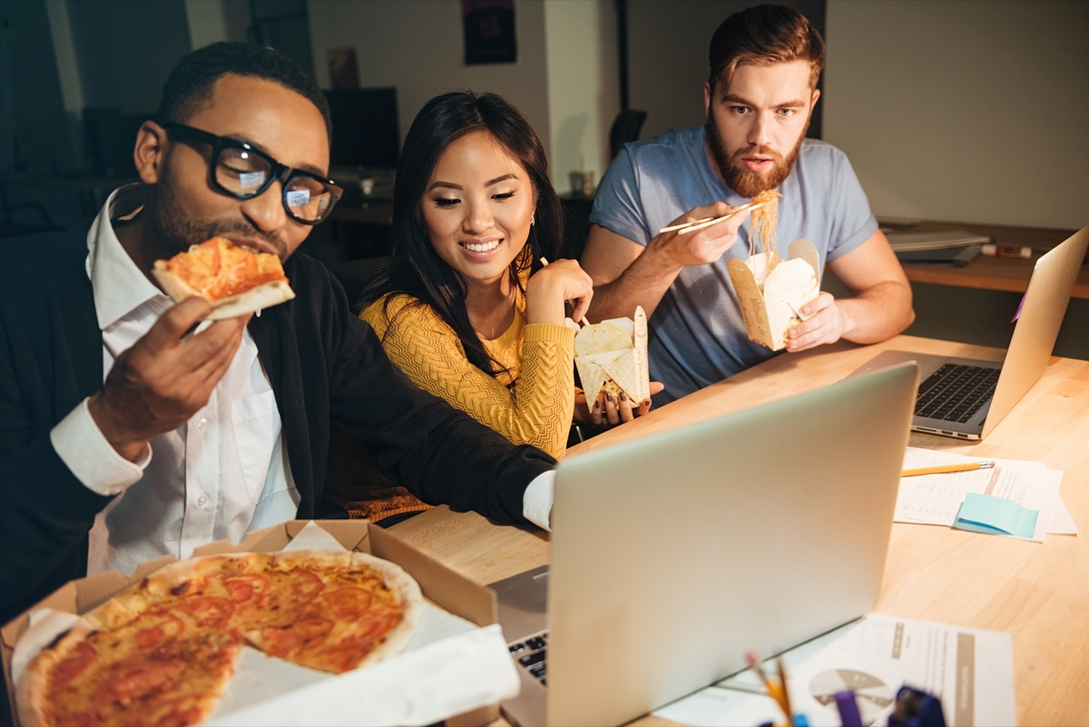 Three young coworkers eat pizza late at night, high cholesterol