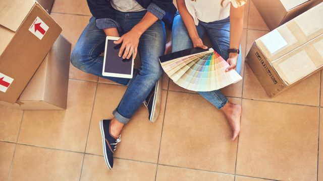 High angle shot of a couple using a digital tablet while looking at color swatches in their new home