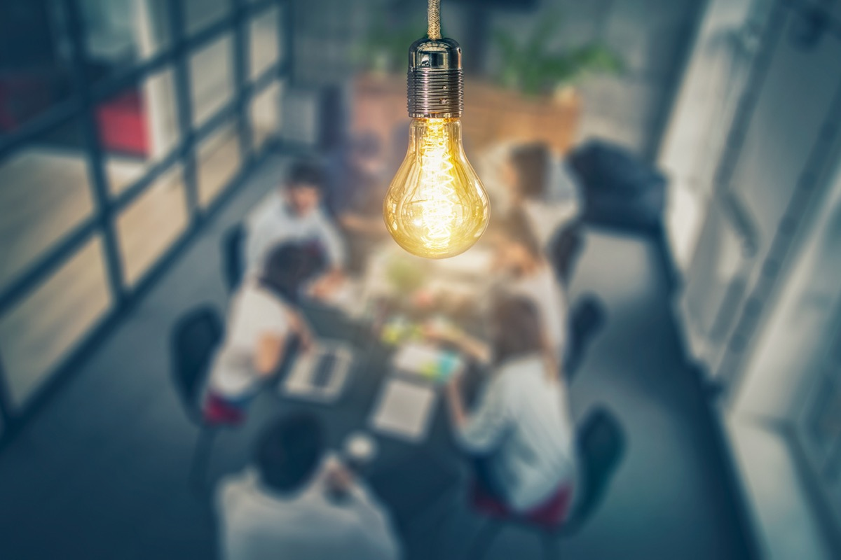 Young business people are discussing together a new startup project. A glowing light bulb as a new idea, MTV voting body