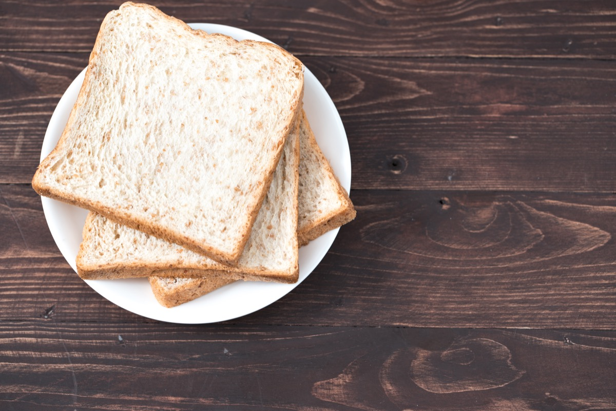 Three slices of white bread on white plate on wooden table, old-fashioned cleaning hacks