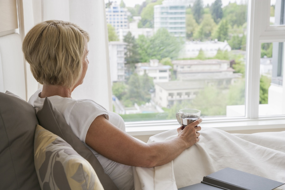 Woman sitting in bed looking out window
