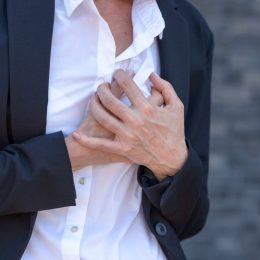 Business woman having a heart attack and grabbing her breast in a close up view