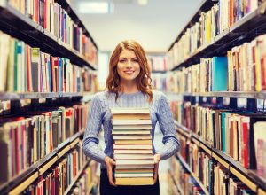 Young woman standing in library aisle holding stack of books