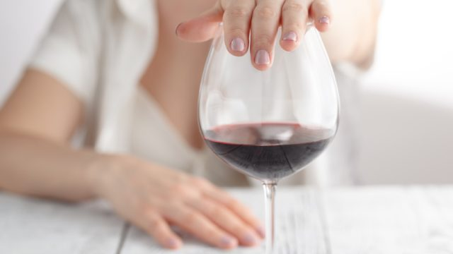 Woman's Hand on Glass of Wine