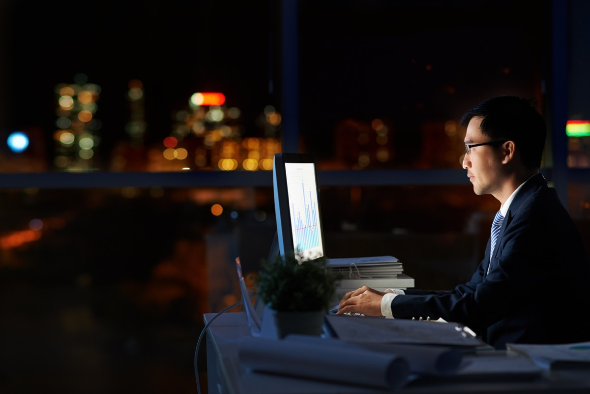 Man Working Alone in a Dark Office at Night