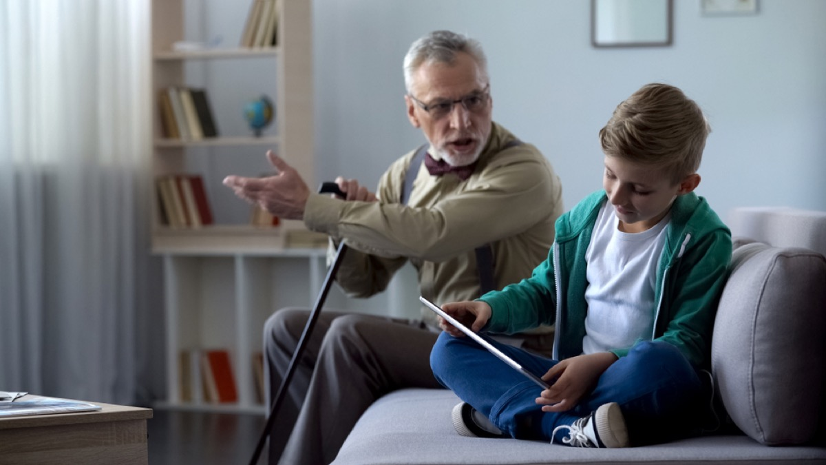 older man yelling at young boy playing on tablet, things that annoy grandparents