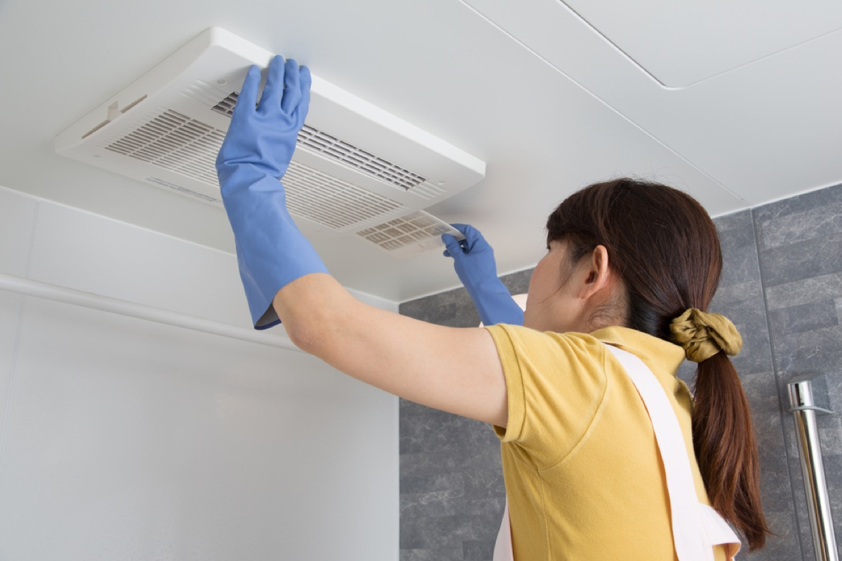 woman cleaning bathroom fan, signs your home is falling apart