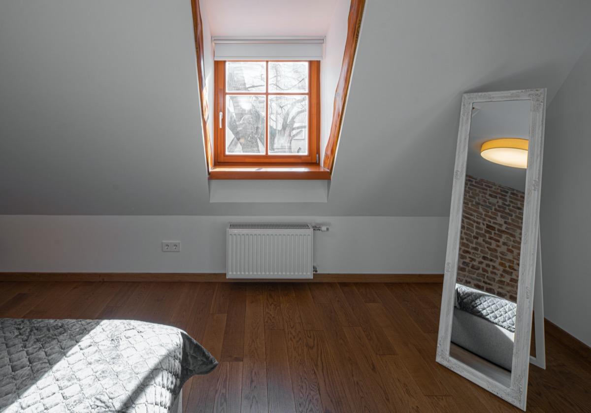 bedroom with mirror, window, and sloped hardwood floor
