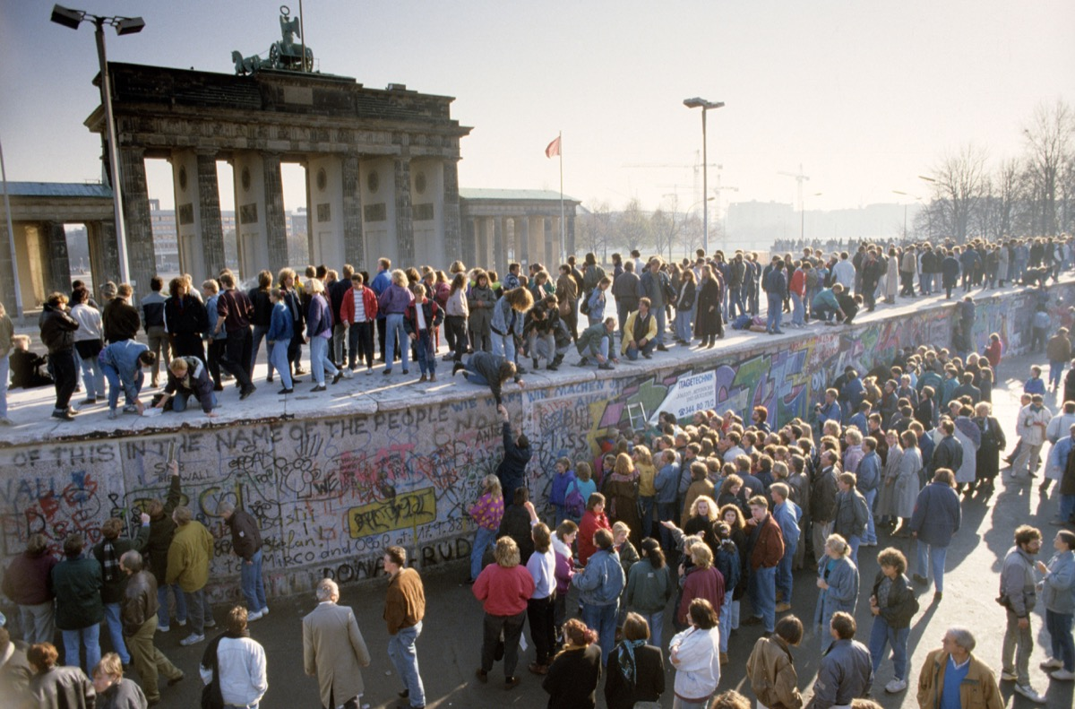 ossis and wessis dancing on top of the berlin wall in 1989