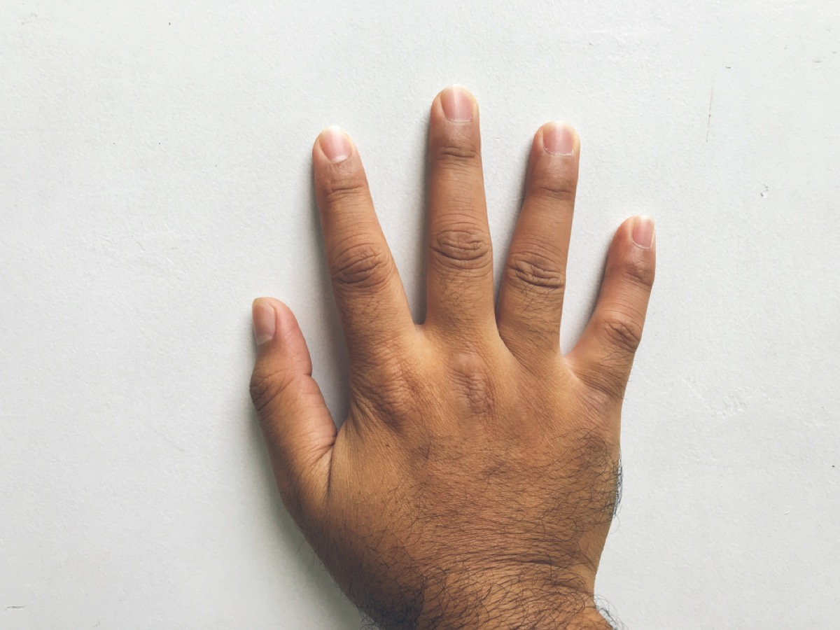 man's hand touching wall, signs your home is falling apart