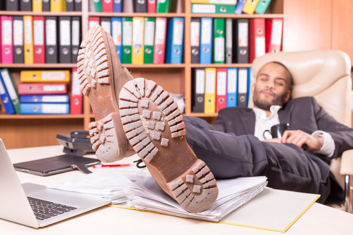 Man at the office bored with his legs outstretched reading body language