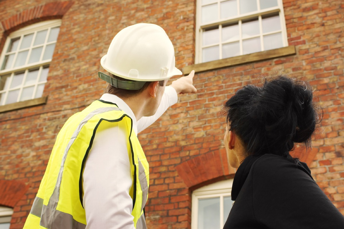 man in hardhat pointing to home's exterior window, signs your house is falling apart