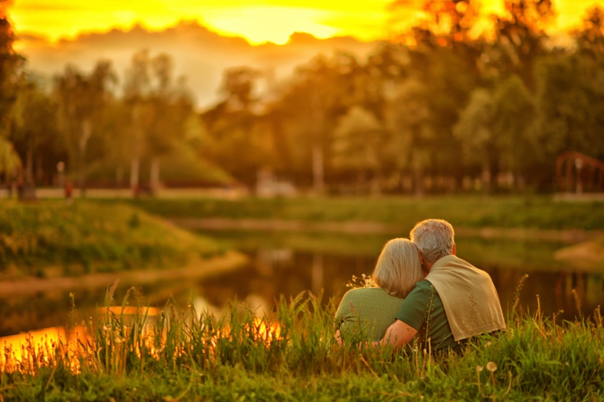 couple sitting in a park at sunset in one of the best us cities for retirement