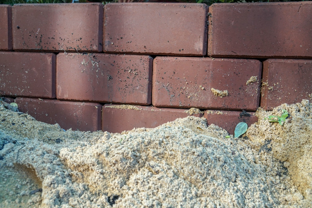 pile of dirt next to the brick foundation of a home