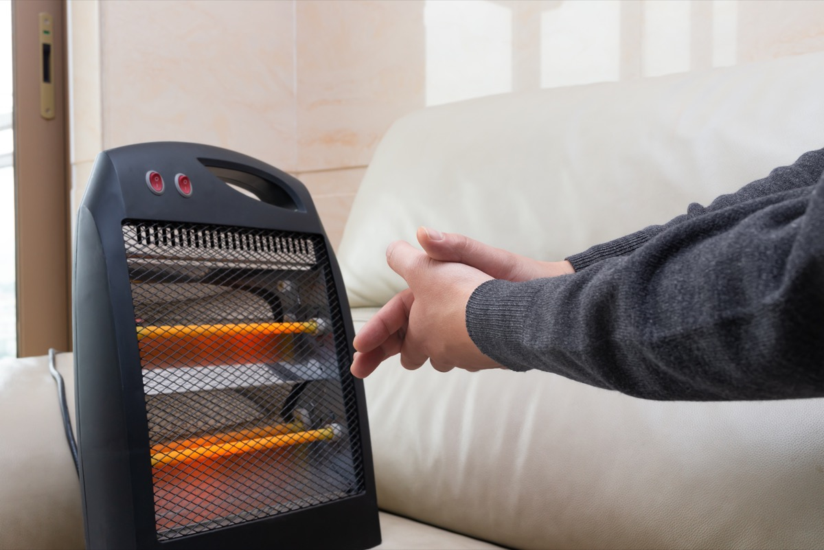 Person Warming Their Hands in Front of an Electric Heater Get Rid of Old Stuff