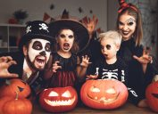 family in halloween costumes standing in front of jack o'lanterns