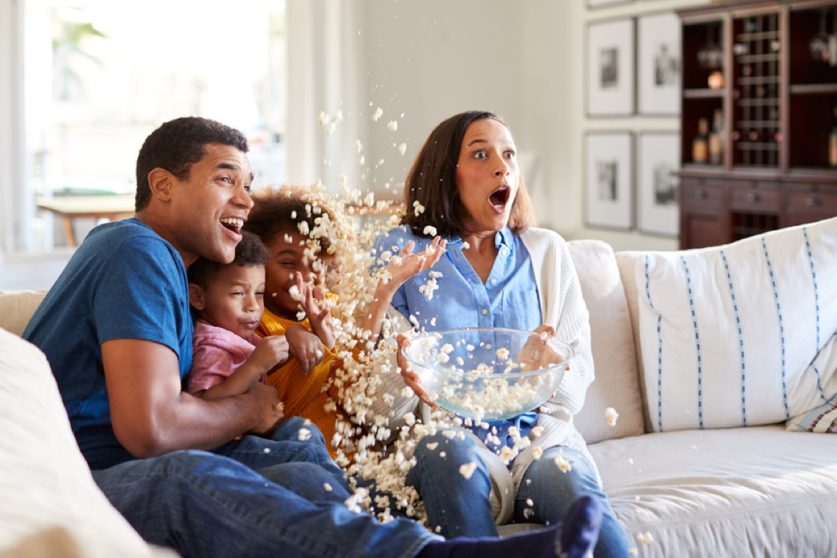 family on the couch watching movie while popcorn spills on the floor, best halloween movies for kids