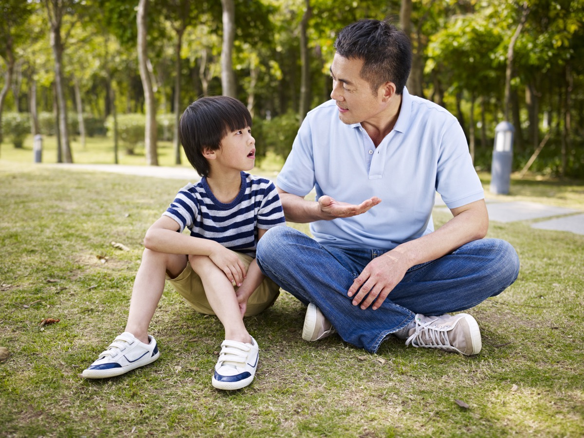 a father and his son sitting on a lawn in a park and talking