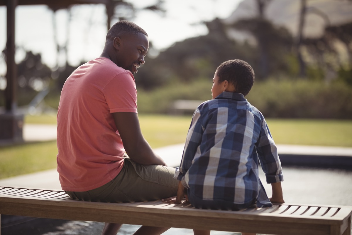a father sitting down next to his son child and talking