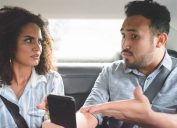 young couple arguing in the backseat of a car while the man points to his phone defensively