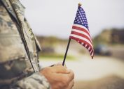 military man holding american flag - veterans day quotes