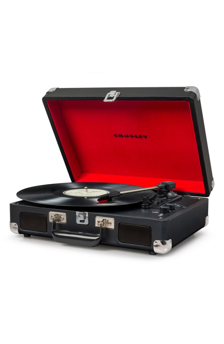 record playing on turntable in black case with red interior