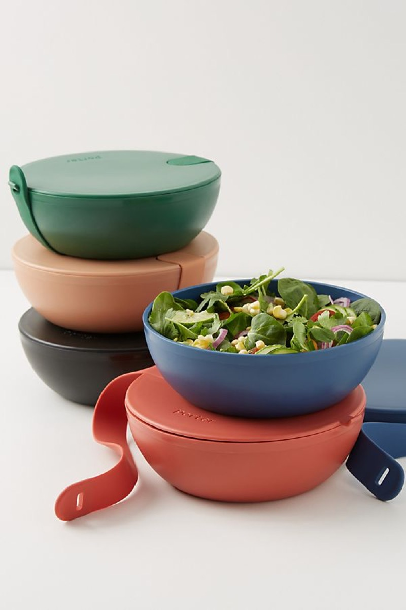 five bowls in different colors, one with salad greens in it