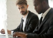 Jealous Male Coworker Looking at a Fellow Employee Things He Won't Admit