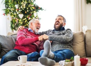 Two men laughing on a couch during Christmas time