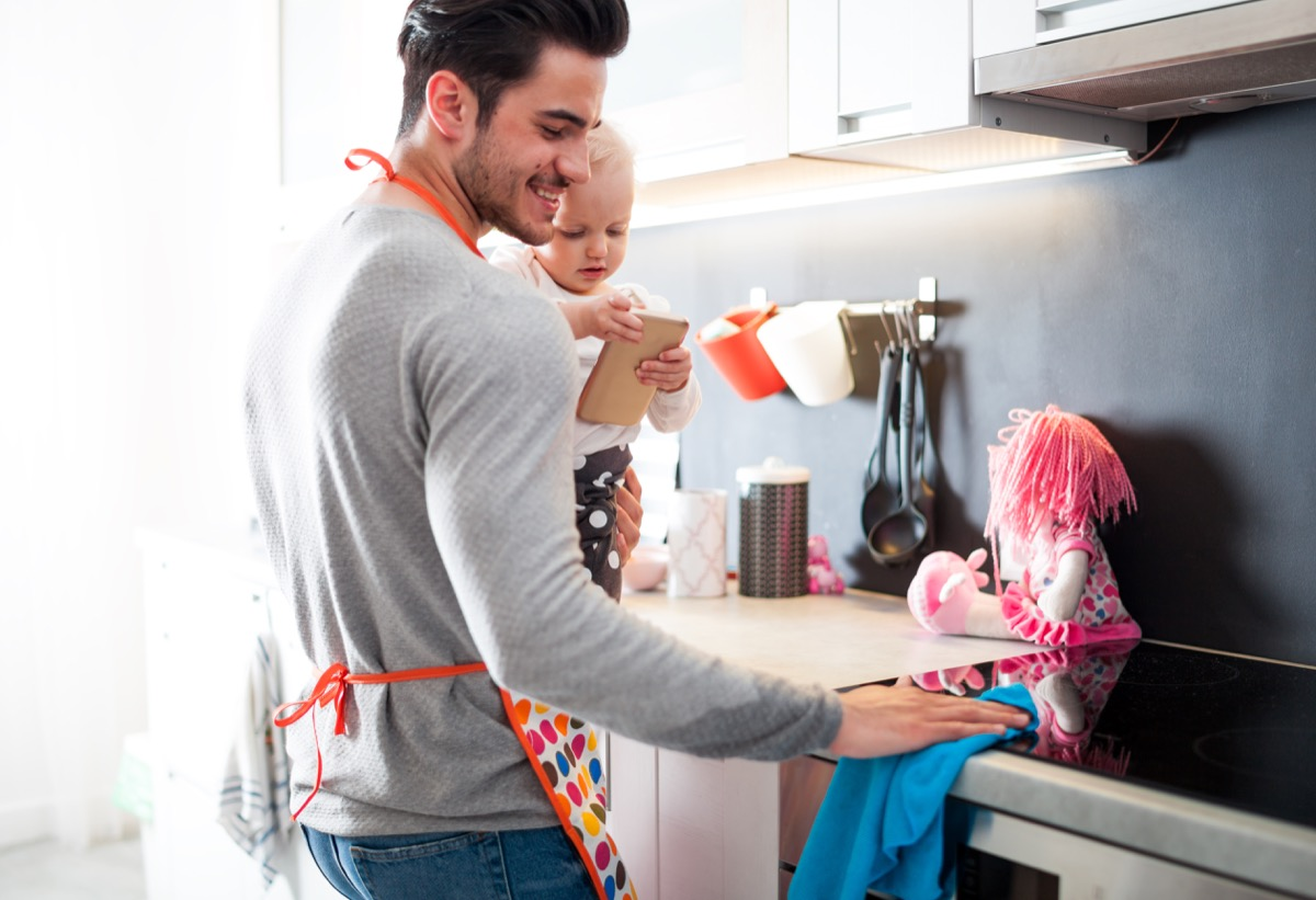 a father and his baby cleaning the kitchen counter