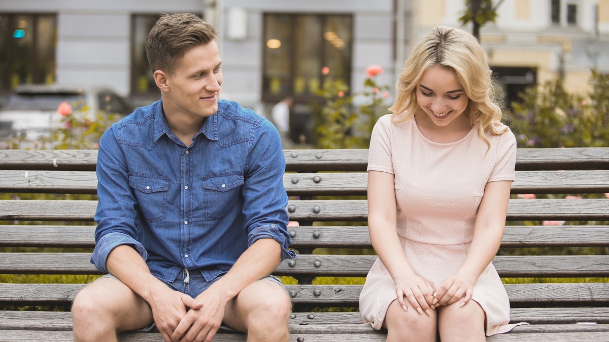 man complimenting woman on bench