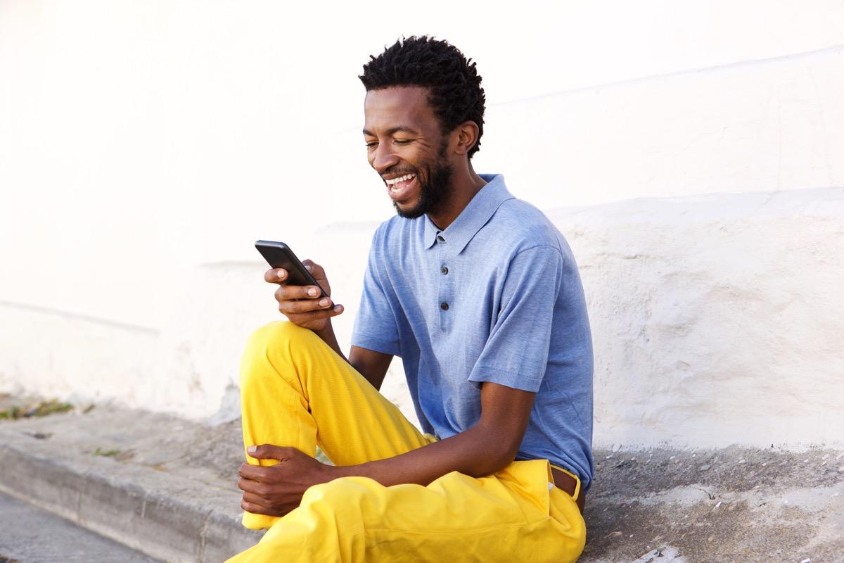 Man looking at phone and laughing
