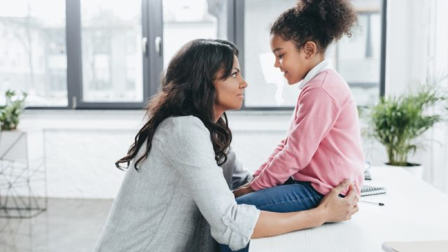mother crouched down talking to daughter sitting on table, prepare children for divorce