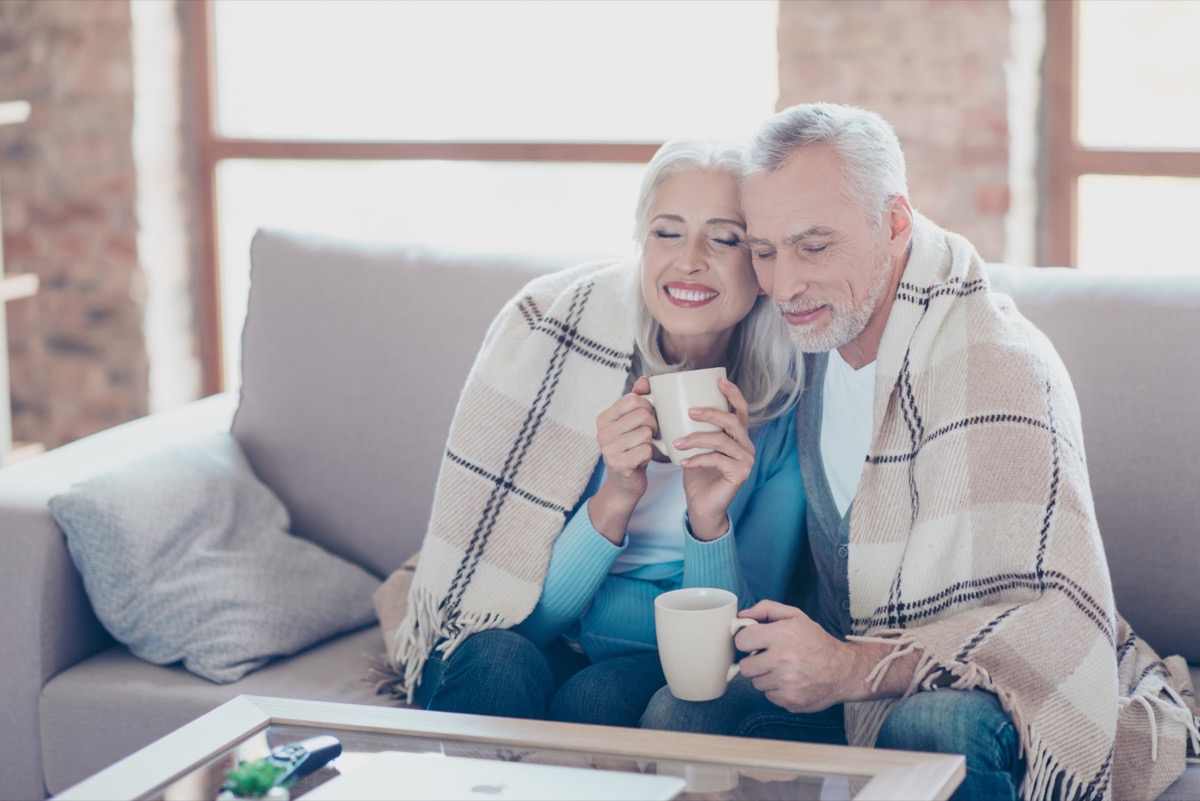 Older couple happily sitting under a blanket in the winter