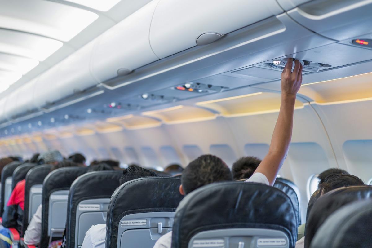 man adjusting plane air vent
