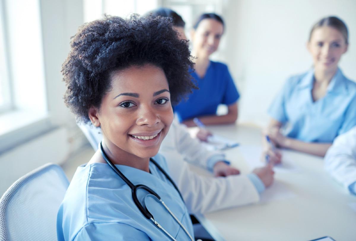 group of nurses and doctors sitting in scrubs at table, school nurse secrets