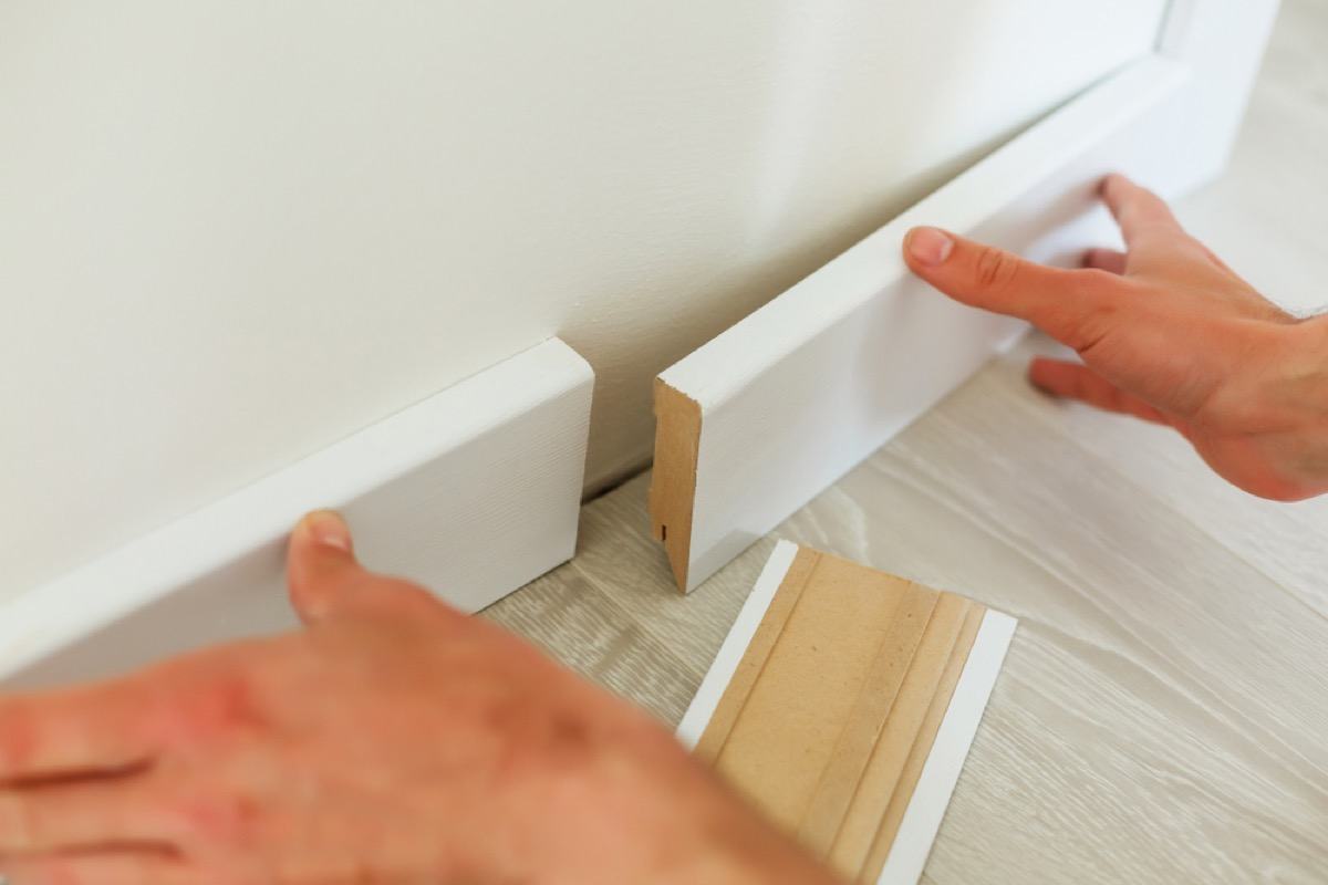 man installing baseboards, signs your home is falling apart