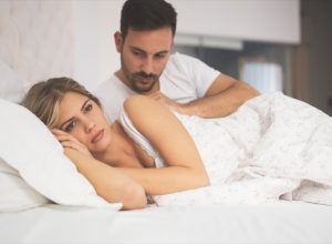 mean and woman in bed looking pensive - what your cheating dream means