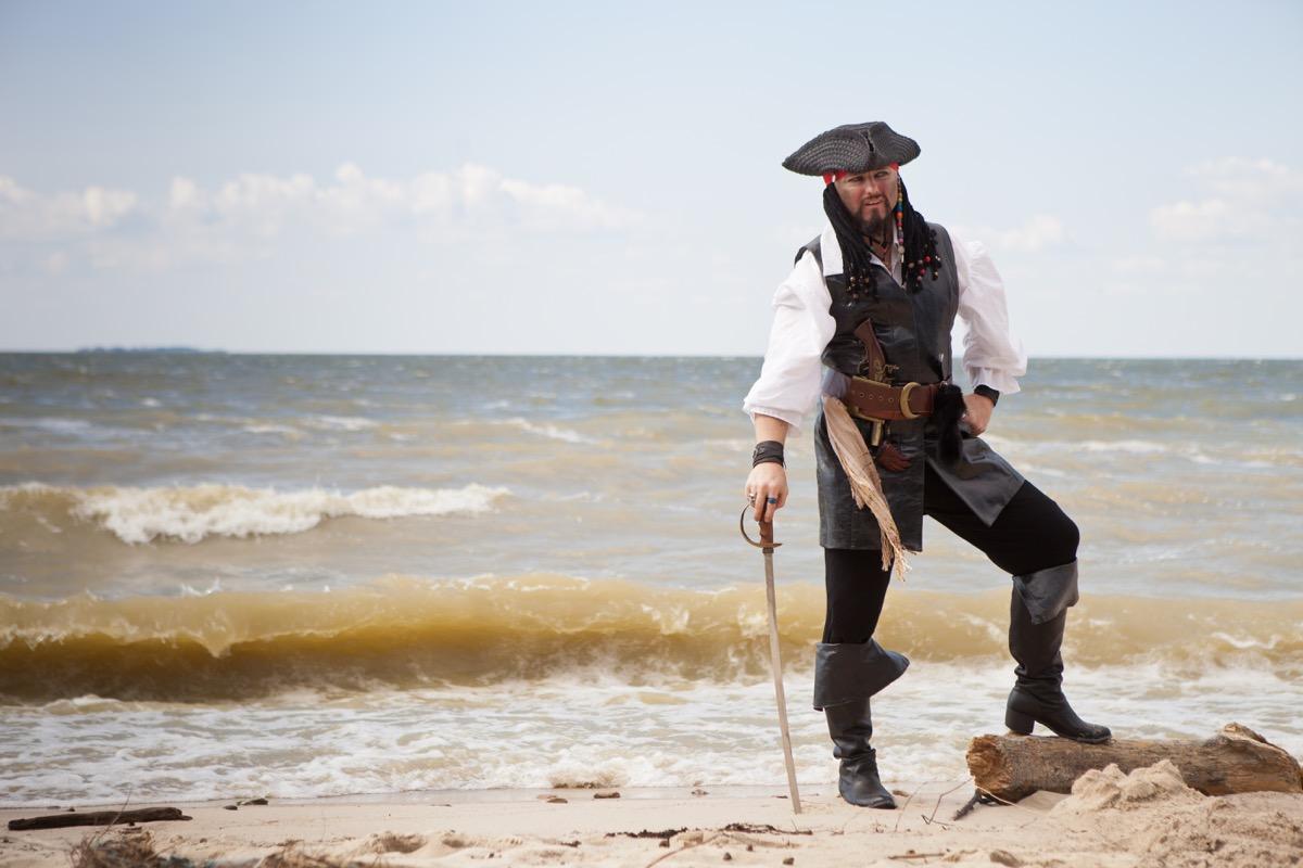 Man dressed as pirate on beach