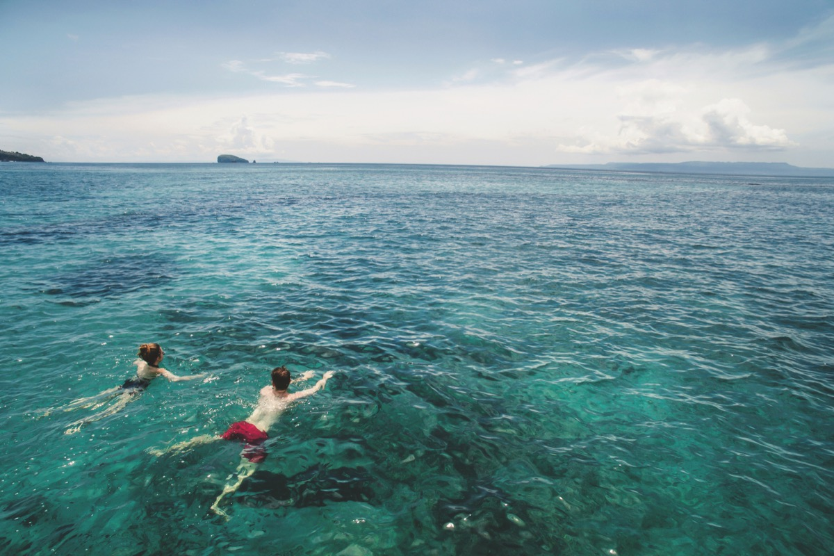 Two people swimming in the ocean