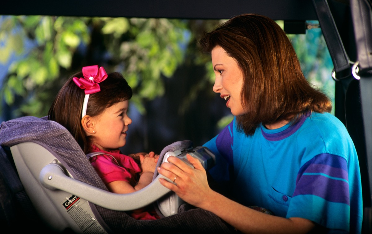 Mom strapping daughter in to a car seat 1990s
