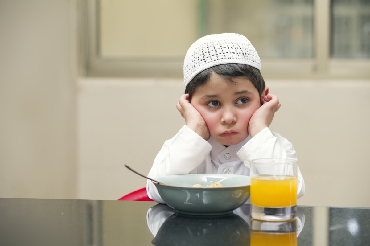 unhappy child eating meal old-fashioned manners