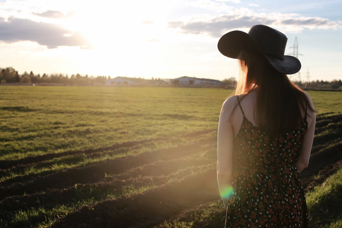 woman wearing a cowboy hat looking out over a field