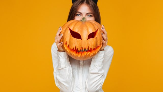 woman wearing cat ears and holding jack o'lantern,