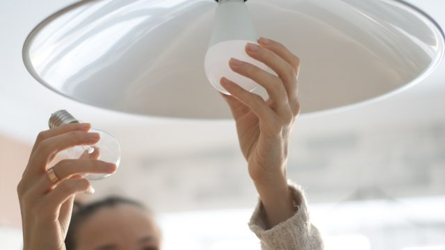 woman installing white lightbulb in home, property damage