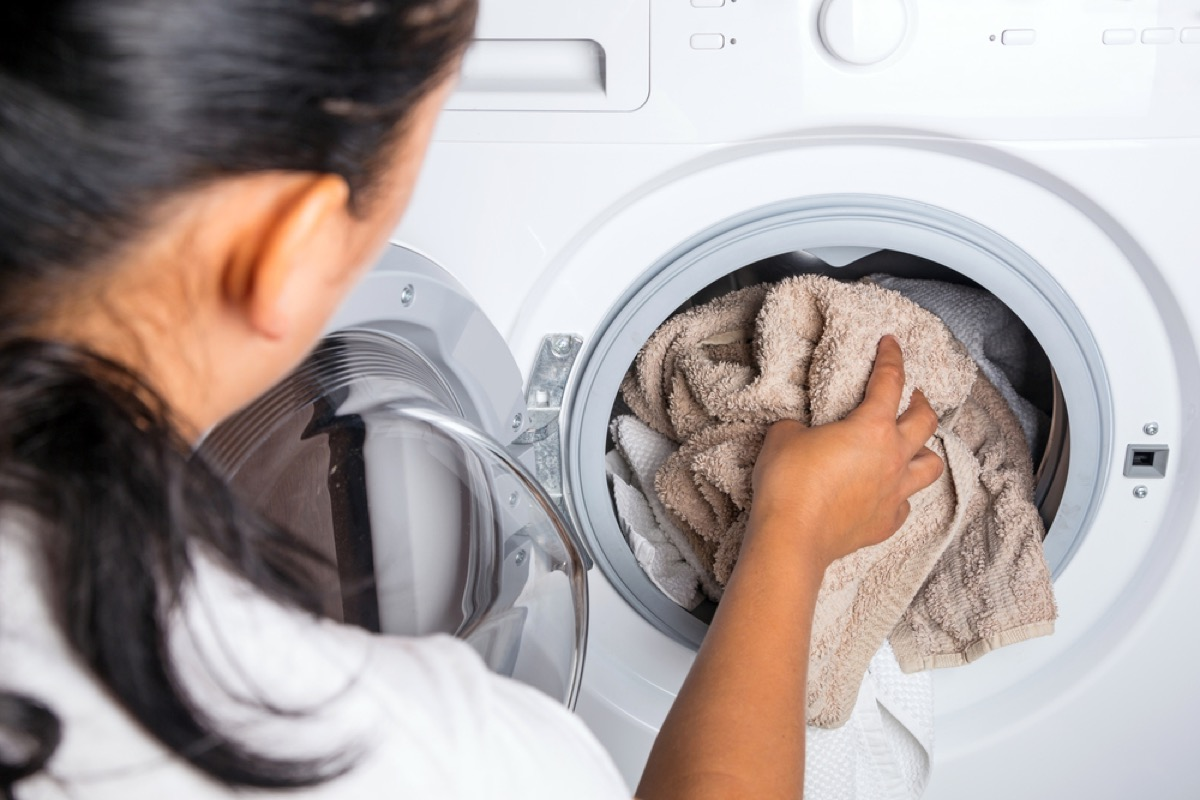 woman putting towel in washing machine, old school cleaning tips