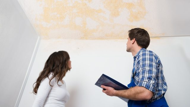 white woman and man looking at stained ceiling