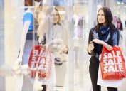woman standing in front of store window holding red shopping bag with sale on it