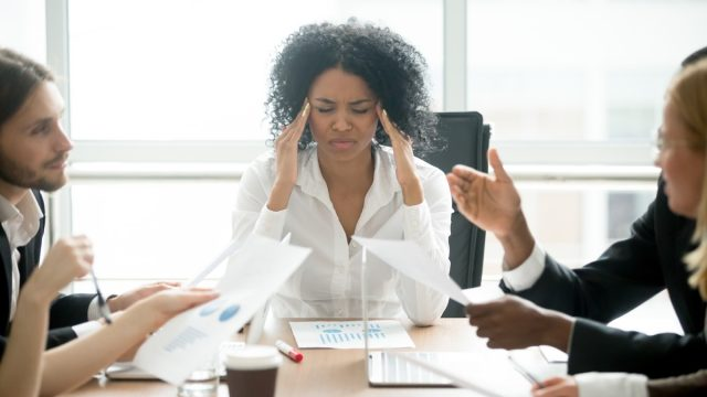 Woman stressed at her desk at work, things husband should notice